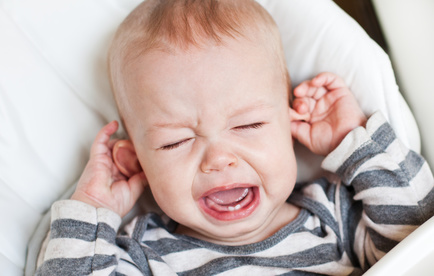 cute little boy crying holding his ear