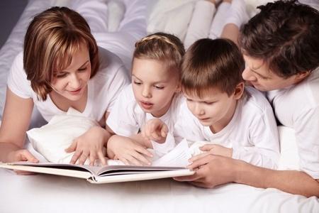 寝る前にベッドで絵本を読む親子